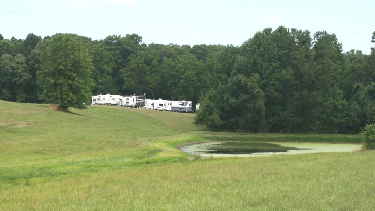 a field with trees and campers/recreational vehicles in the distance