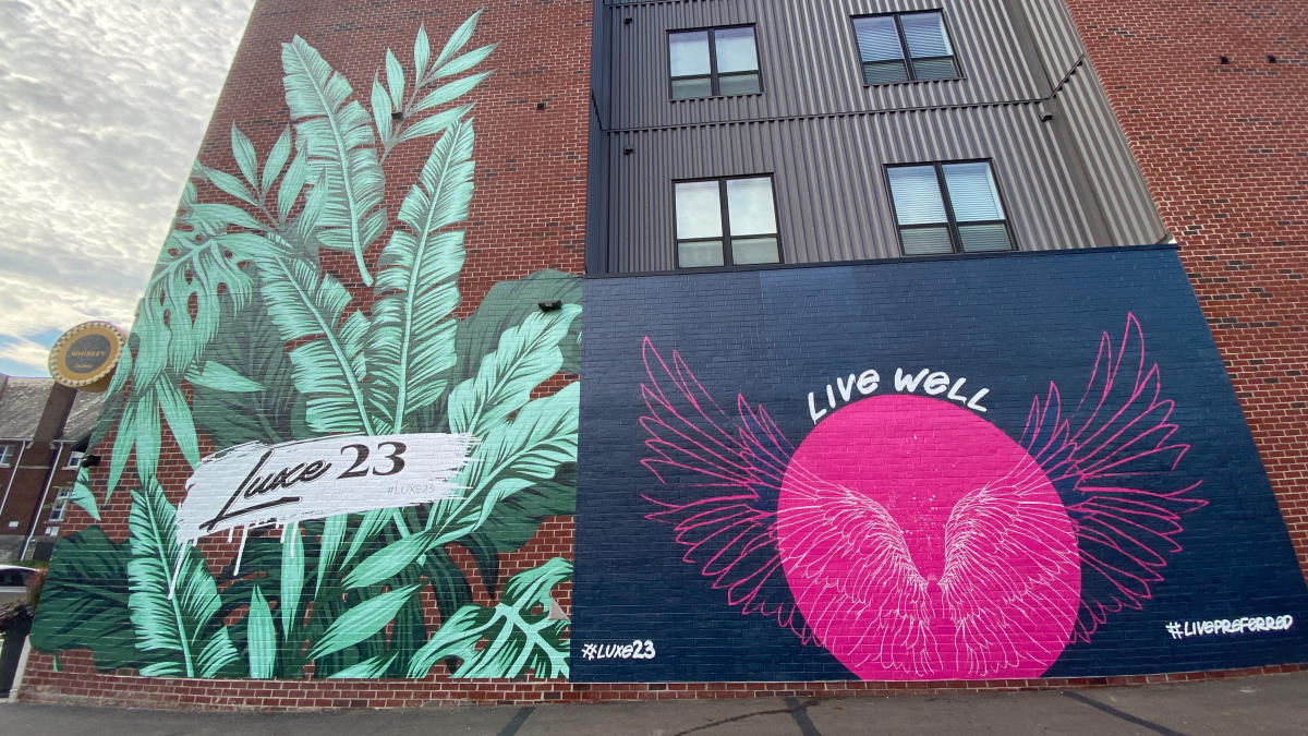 Live Well mural and art on the side of Luxe 23 building