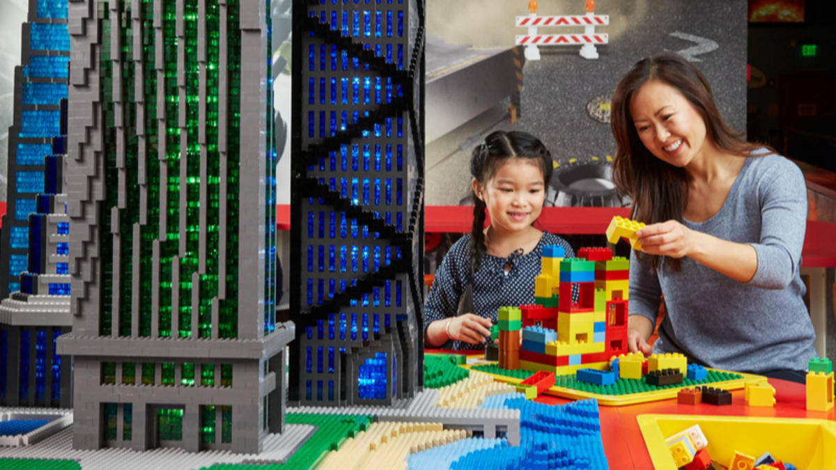 Mother and daughter playing with legos next to lego buildings at LEGOLAND Discovery Center