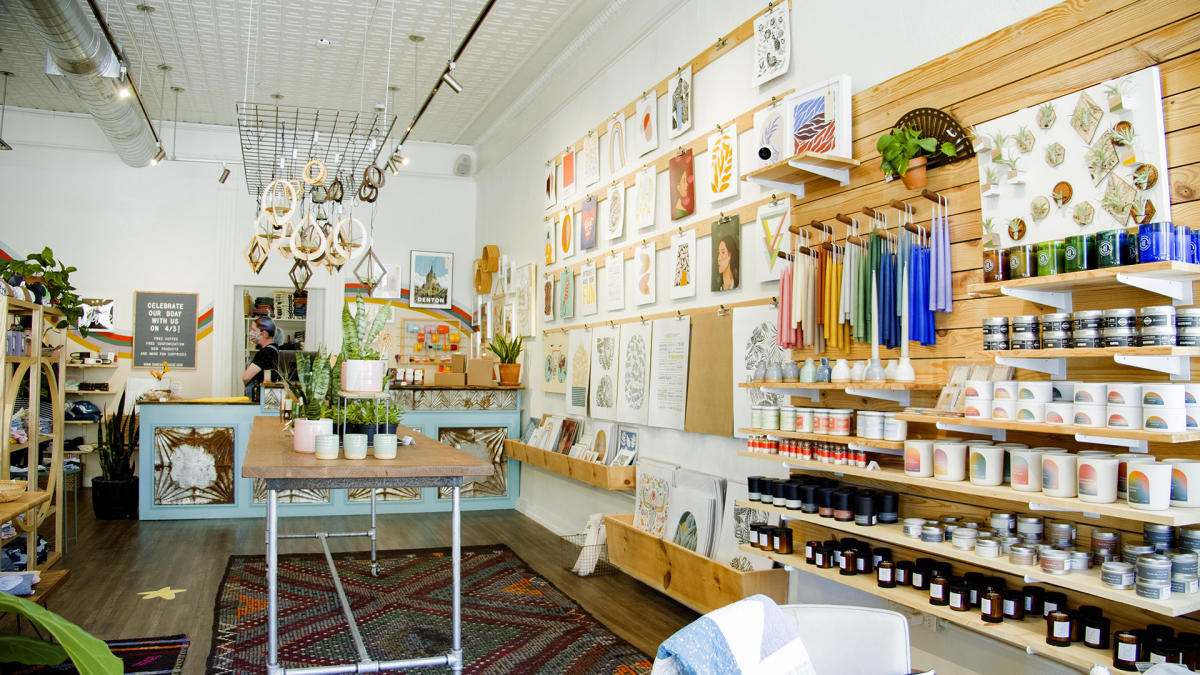 Candles, artwork, and plants shop display inside The DIME Store