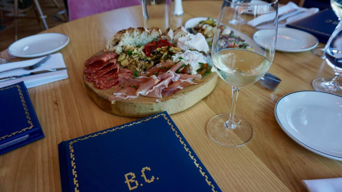 Charcuterie board and wine on a table at Bar Corallini