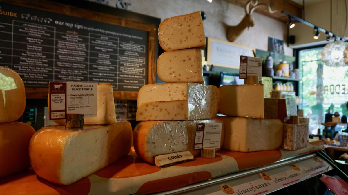 Different varieties of cheese stacked on the counter at Fromagination