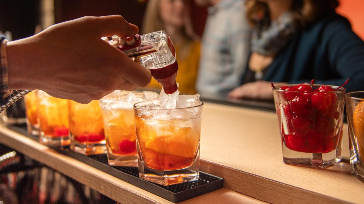 A bartender makes a row of Old Fashioneds at Tornado Room