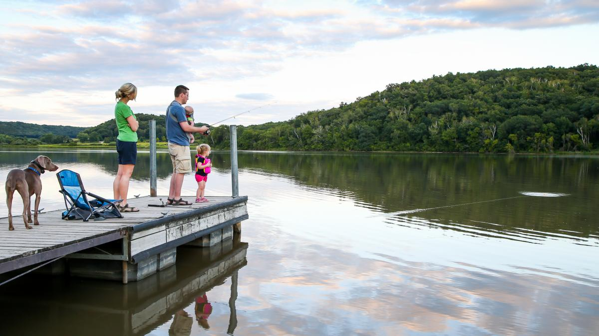 A family fishes off a pier at Indian Lake County Park