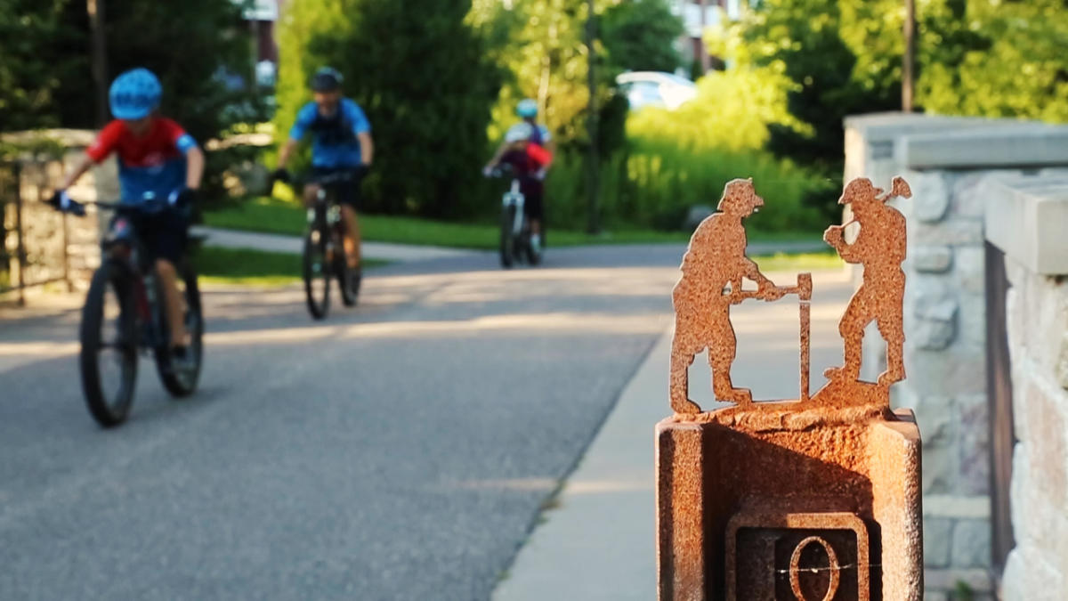Cyclists pedal along the paved surface of the Iron Ore Heritage Trail.
