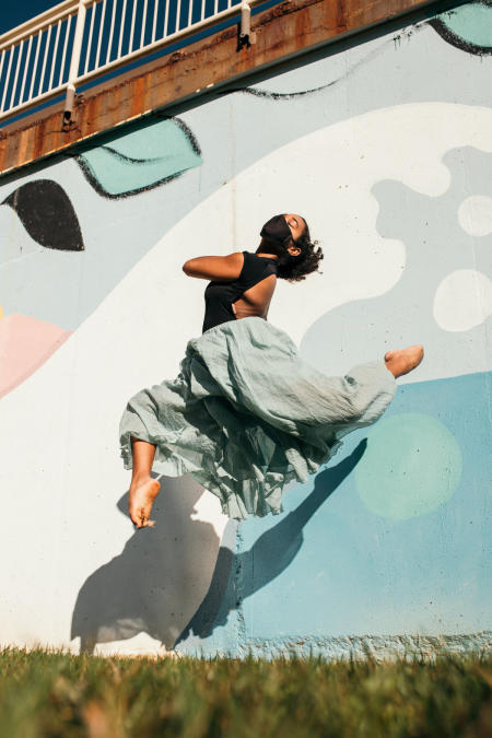 A dancer from the Company at MC 3 jumps in front of a graffitti wall.