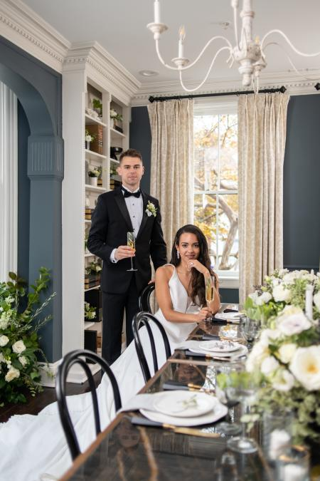 A bride and groom pose for a photo in a luxe dining room