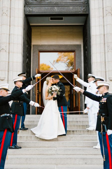 A couple kisses on the steps of the US Naval Academy Chapel with military salute.