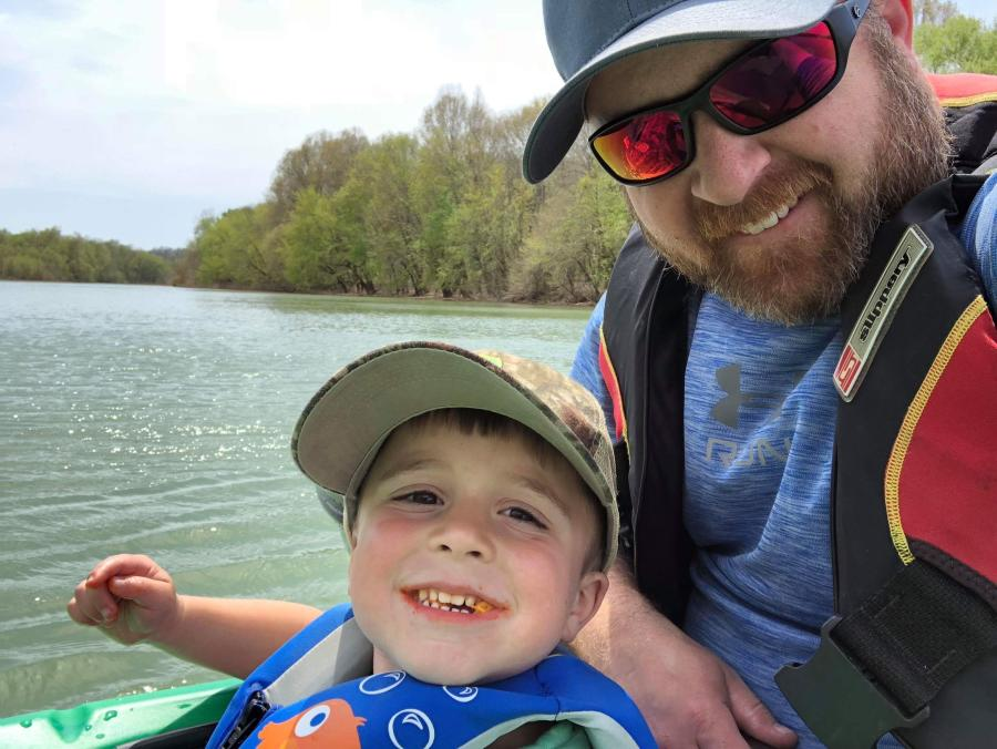 man and son in a kayak on a river