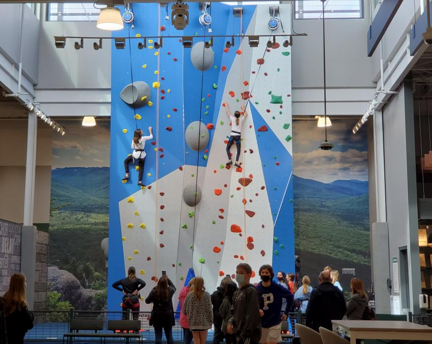 Two people climbing a blue and gray rock wall while a group of people watch at the bottom