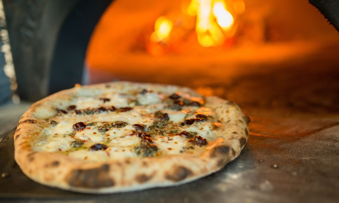 Cooked pizza in front of wood burning oven
