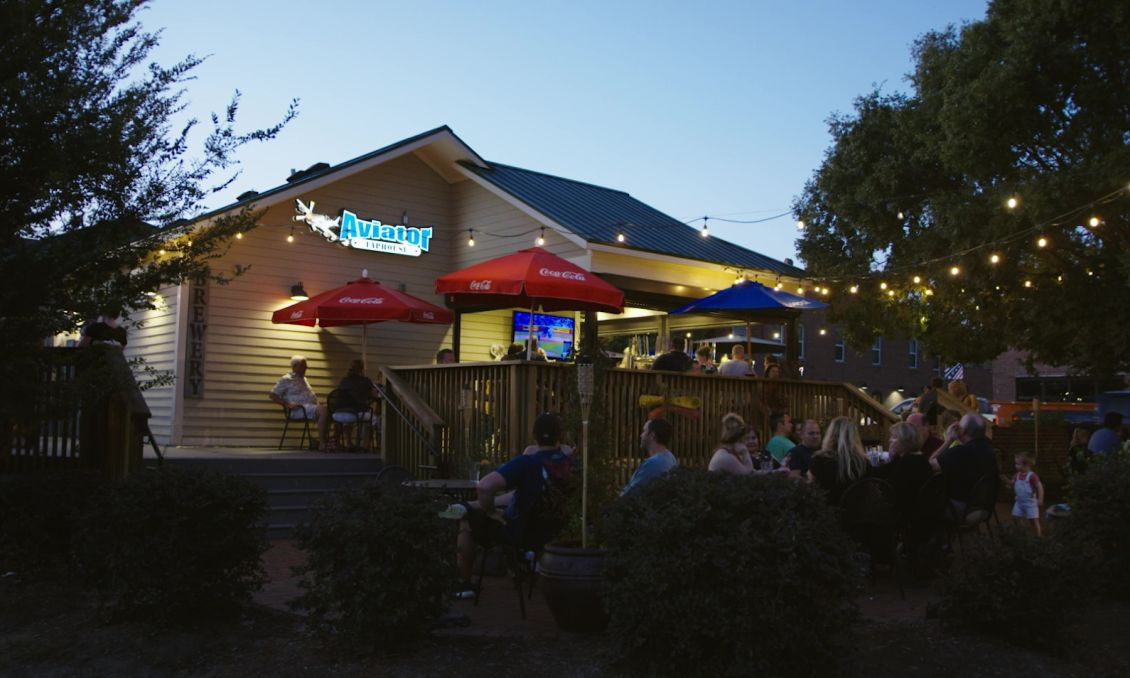 Aviator Brewing Tap House outdoor patio with stringed, handing lights and a lively crowd