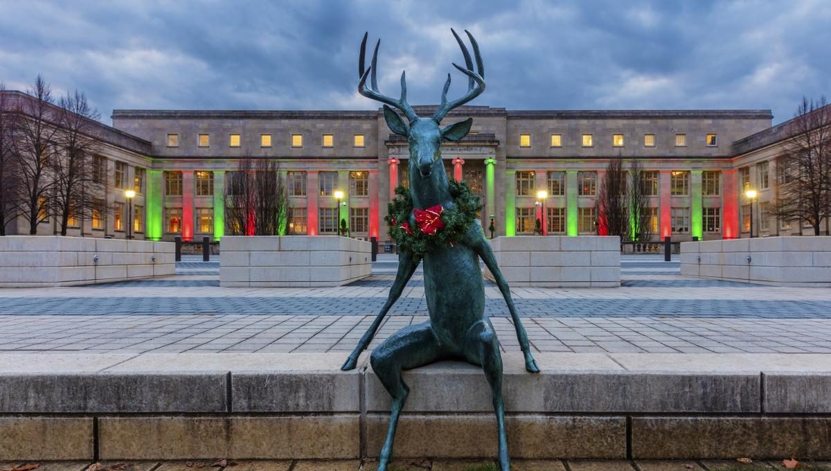 Scioto Mile deer sculpture decked for the holidays with wreath in front of COSI lit with festive holiday lights