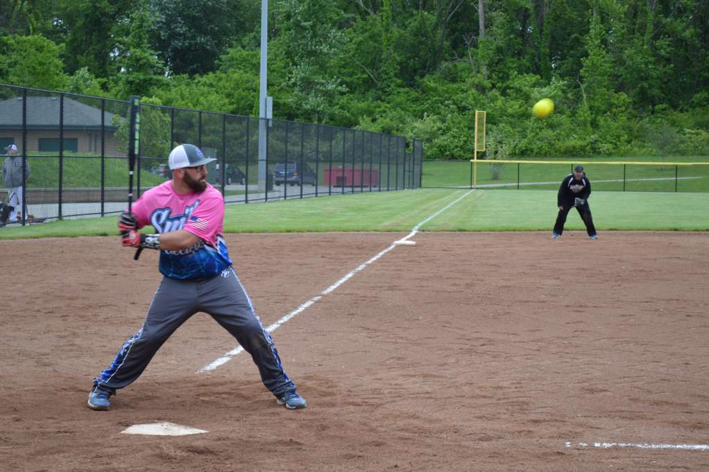 ϾA batter takes a swing in a softball tourney}}