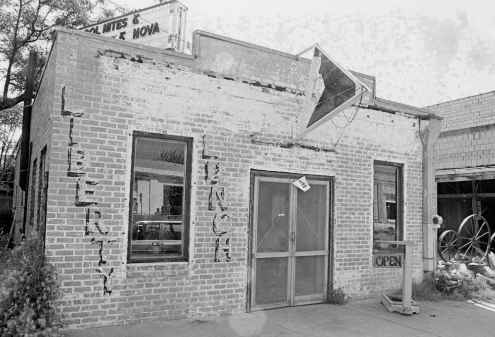 Photo of exterior view of the Liberty Lunch nightclub It is a small brick building with faded paint