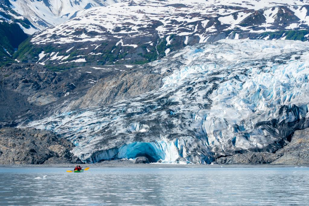 a kayaker paddling in front of a tidewater glacier
