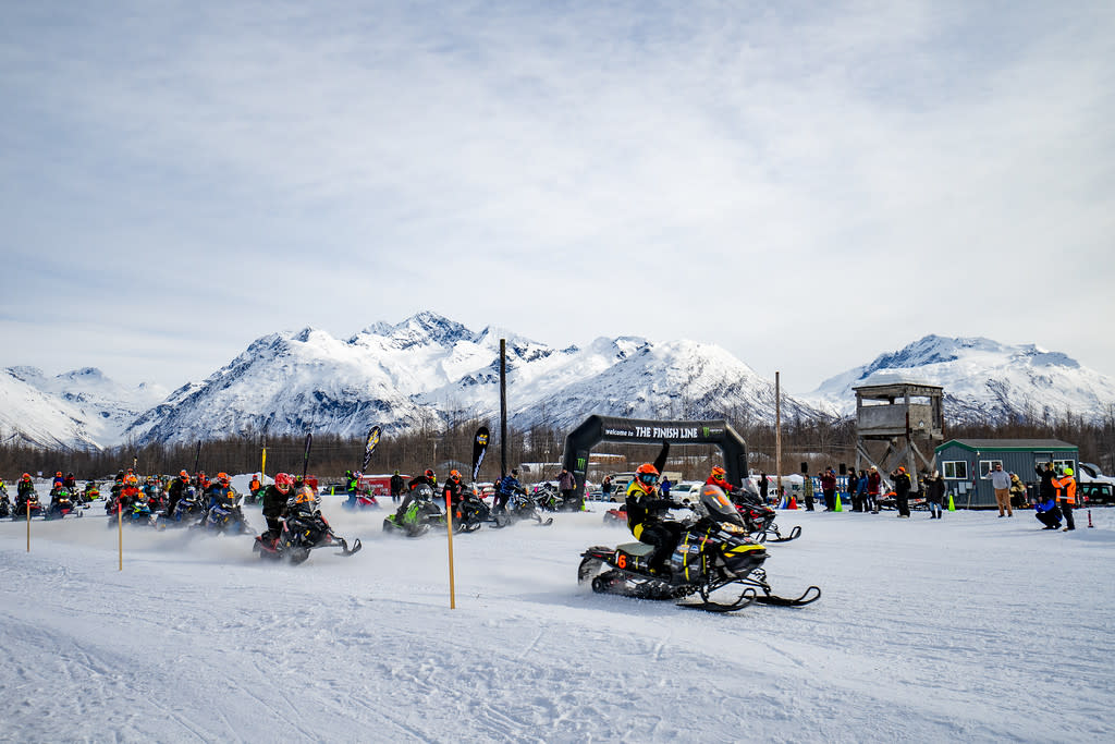 snowmachine racers take off from a start line