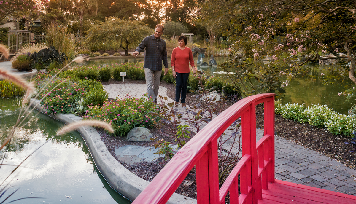 A couple walking through the New Hanover County Arboretum Japanese garden in Wilmington, NC