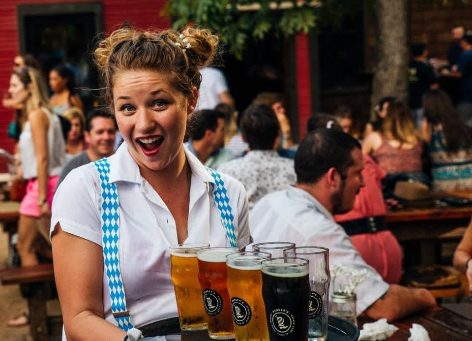 Woman wearing a white shirt and blue suspenders holding a platter of beer at Banger's Oktoberfest
