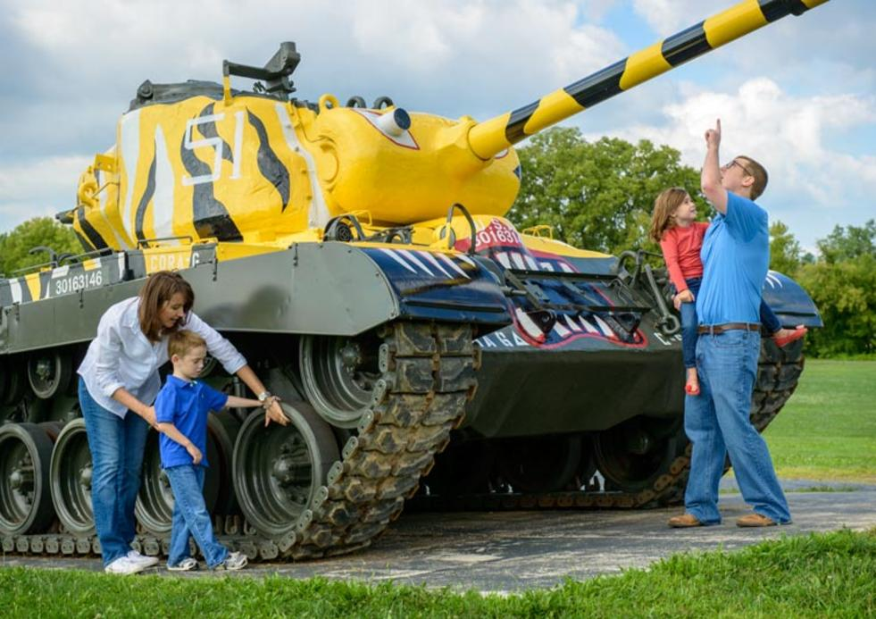 Family looking at the yellow & black army tank at the Army Heritage Trail