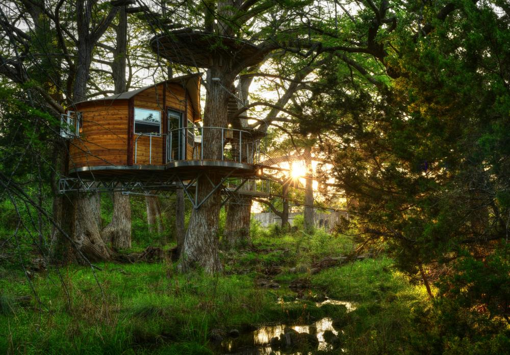 Photo of a treehouse retreat among the trees and overlooking a small creek at Cypress Valley