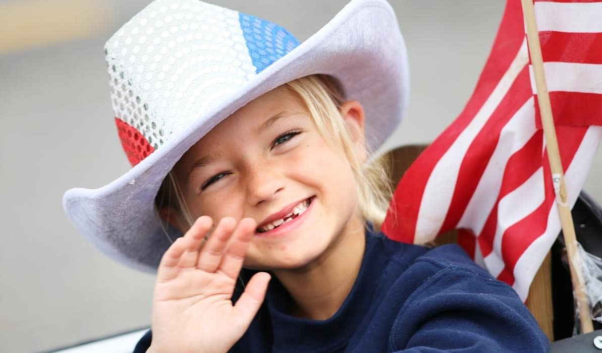 Little girl with a red, white and blue cowboy hat waving to the crowd at the Farragut parade