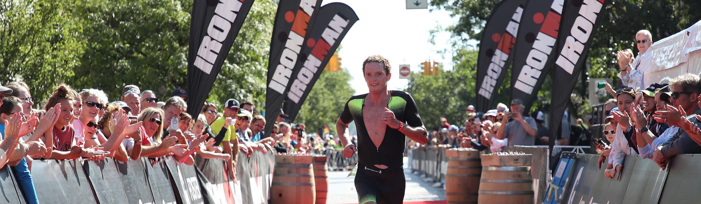 man running across finish line in Ironman race