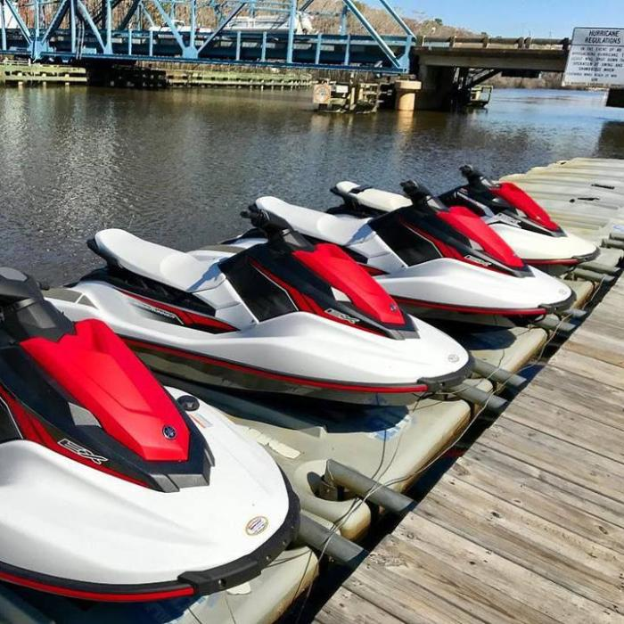 Jet skis lined up near the swing bridge at Island Adventure Wstersports