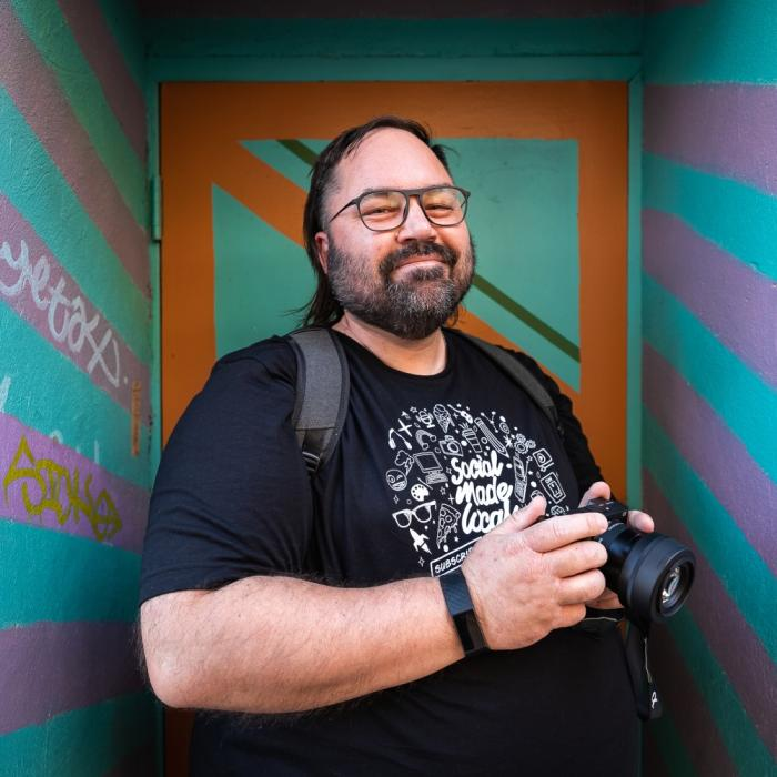 A man with a camera in front of a colourful entry way.