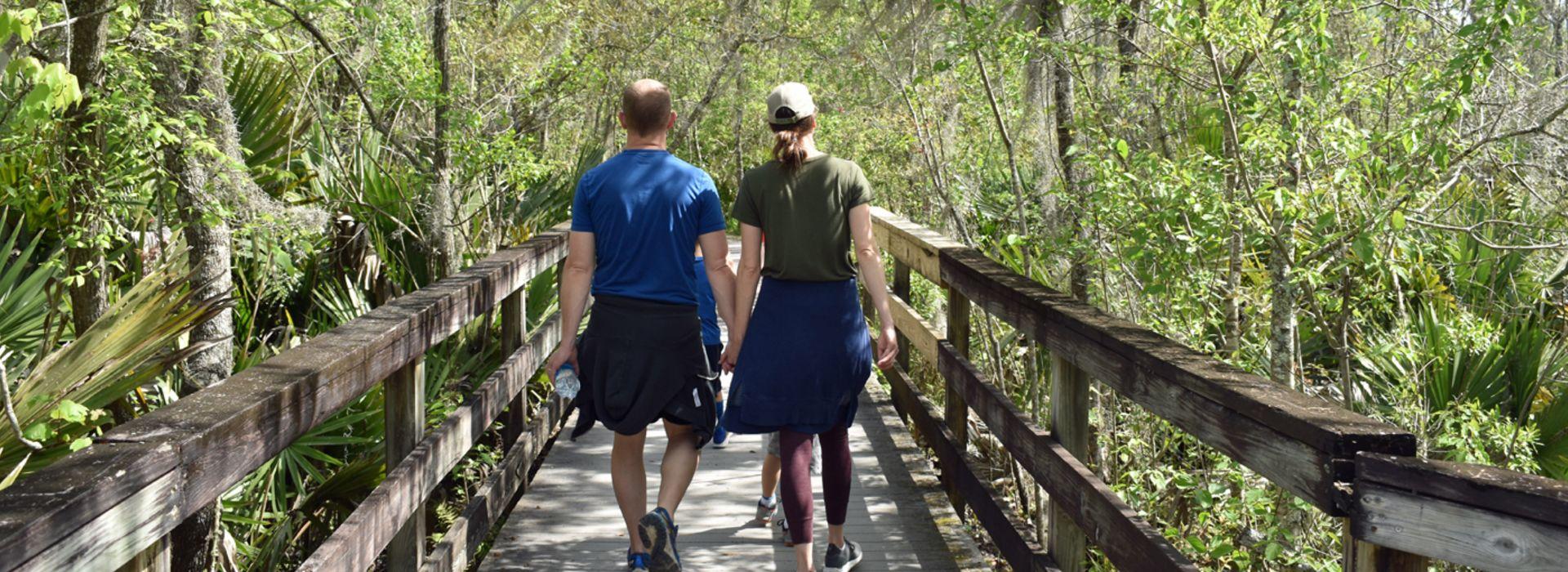 Couple walking on the boardwalk through Barataria in Jefferson Parish