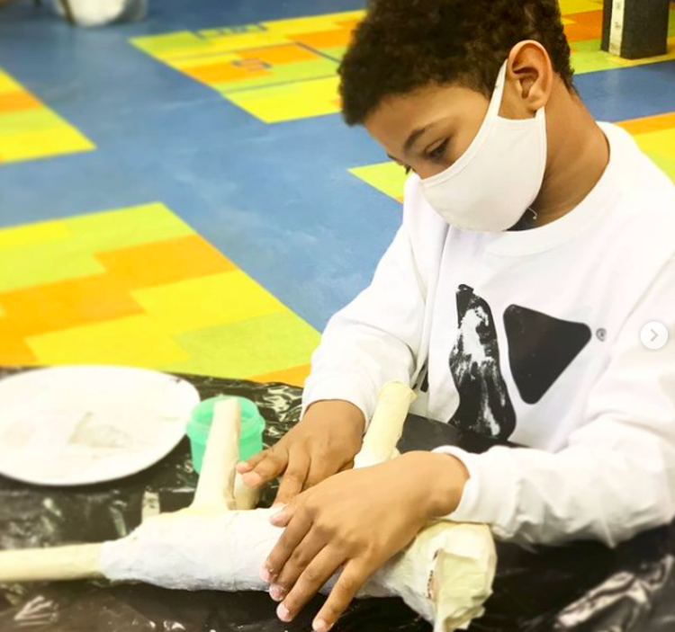 Kid building sculpture in arts and craft
