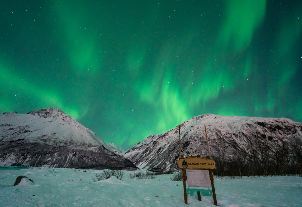 aurora over a frozen lake and mountains