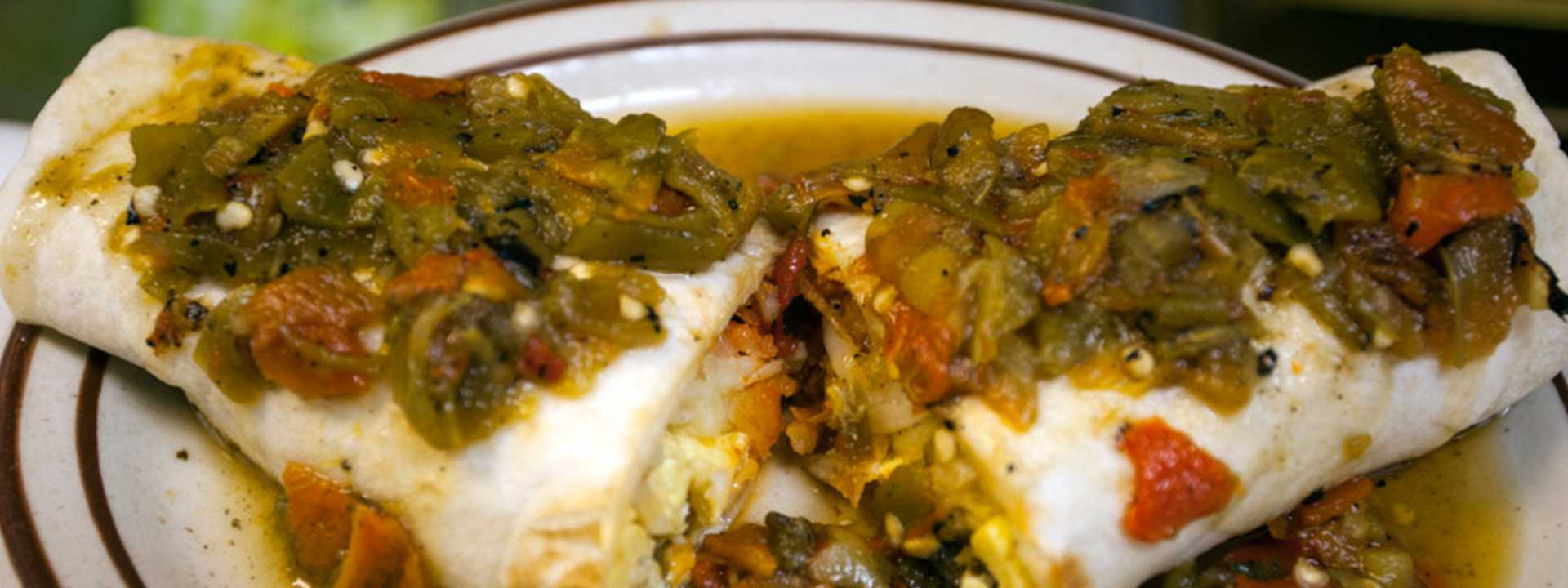 An enchilada topped with freshly-roasted hatch green chilies.