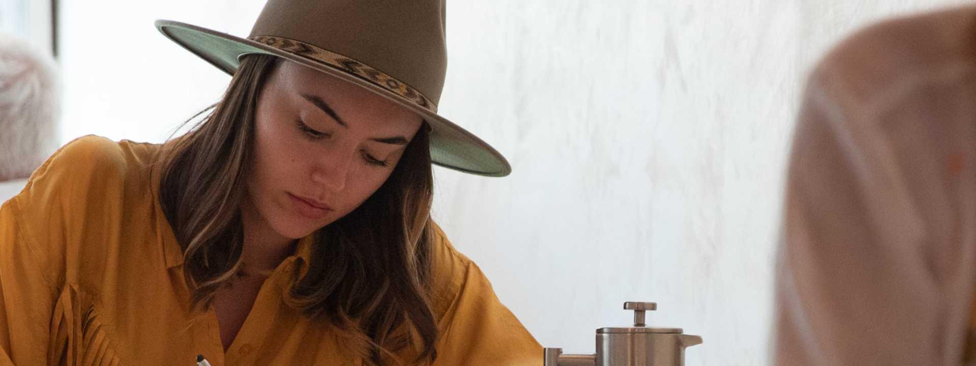 woman in coffee shop writing