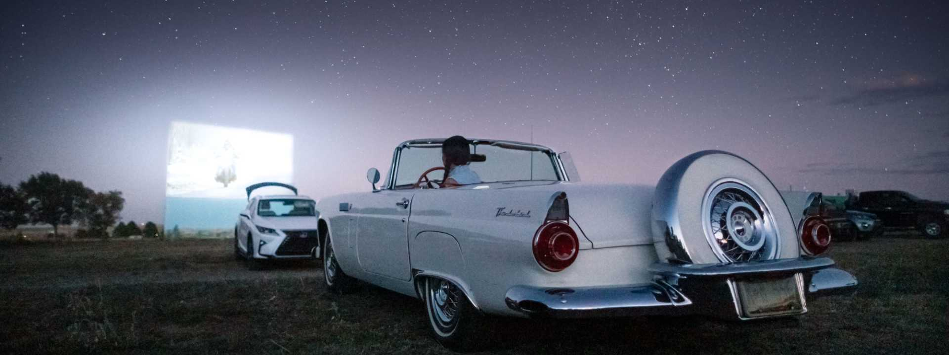 A vintage car at a drive in theater