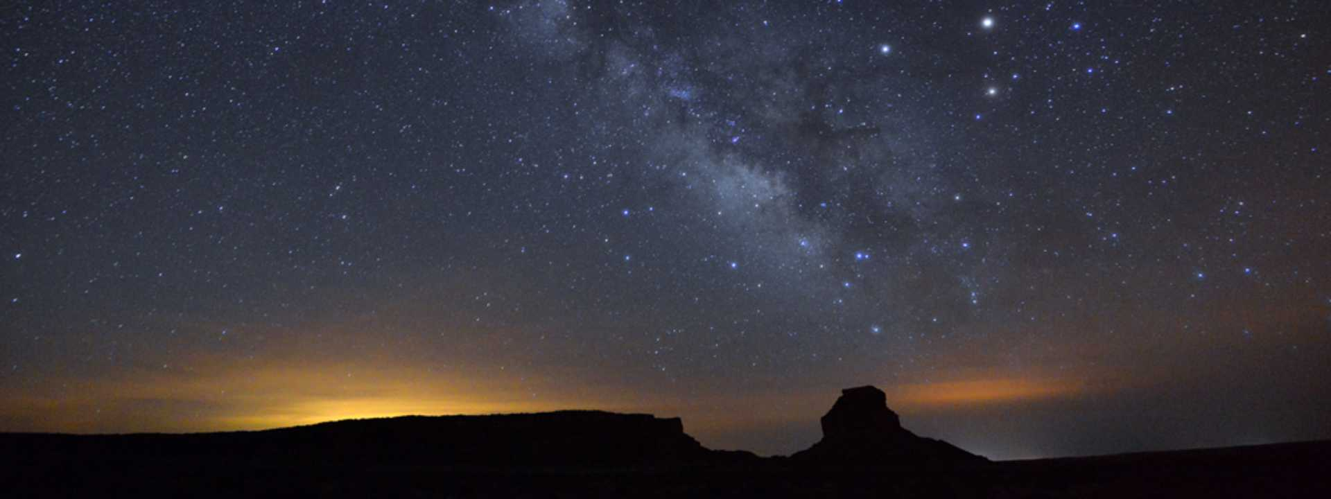 The Milky Way lights the night sky over Chaco Canyon at night.