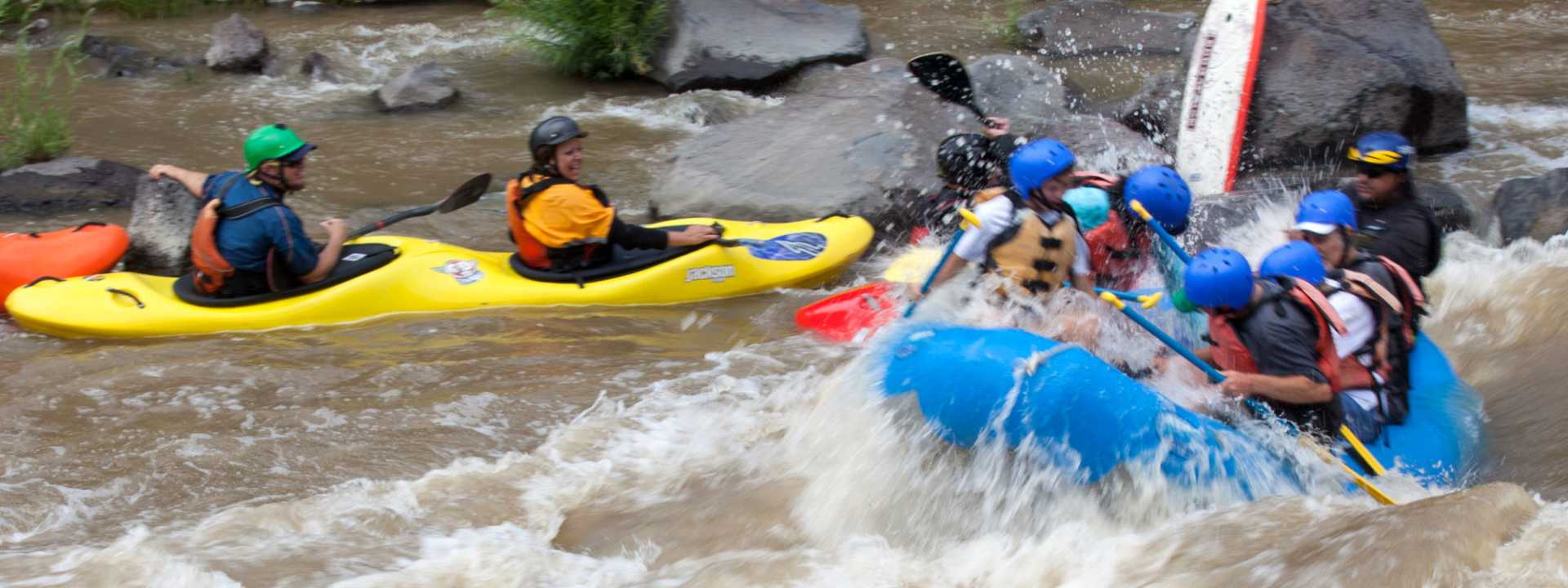 A group travels down the white-water rapids of the Rio Grande River via kayak and river raft.