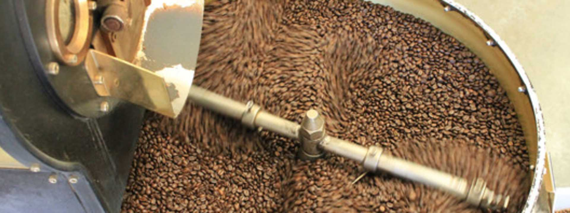 Freshly-roasted coffee beans tumble in a large vat.