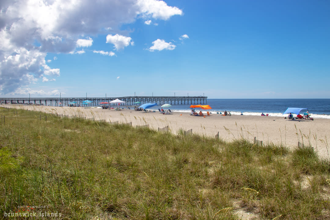 View Of The Pier And Beach Umbrellas At Holden Beach