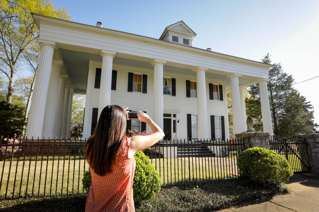 Woman taking picture of historic home in Milledgeville