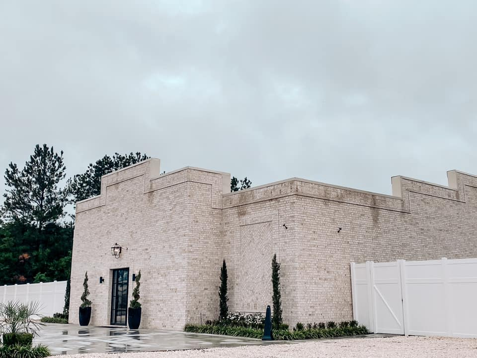 The main entrance at Reign Hills is stately with a white brick exterior.