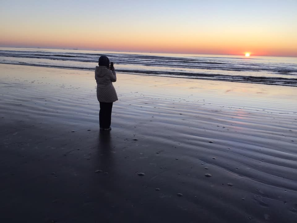 A silhouetted person stands on the beach at sunrise.