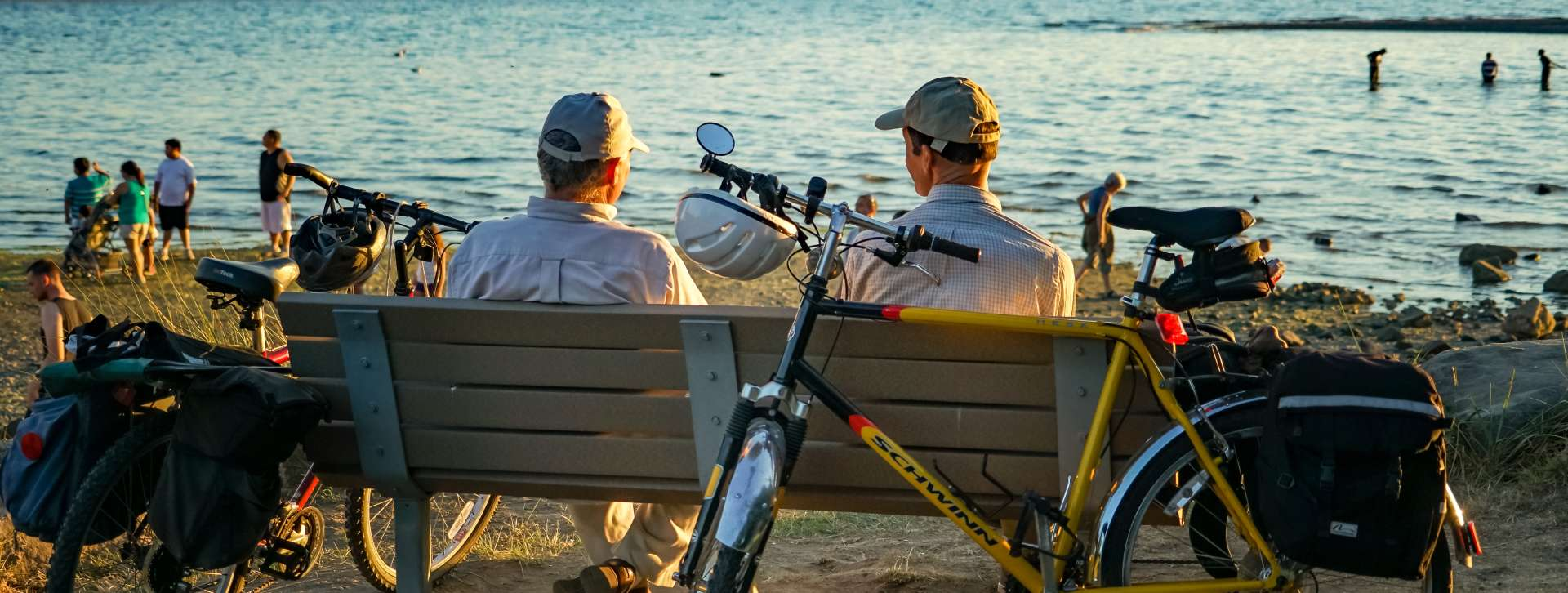 Two friends sitting on bench at Des Moines Beach Park during sunset