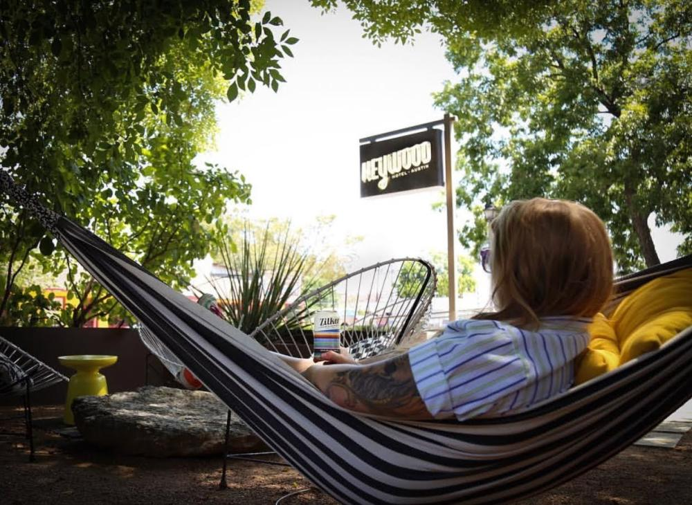 Woman drinking a Zilker Brewing beer in hammock with Heywood Hotel sign behind her in Austin Texas