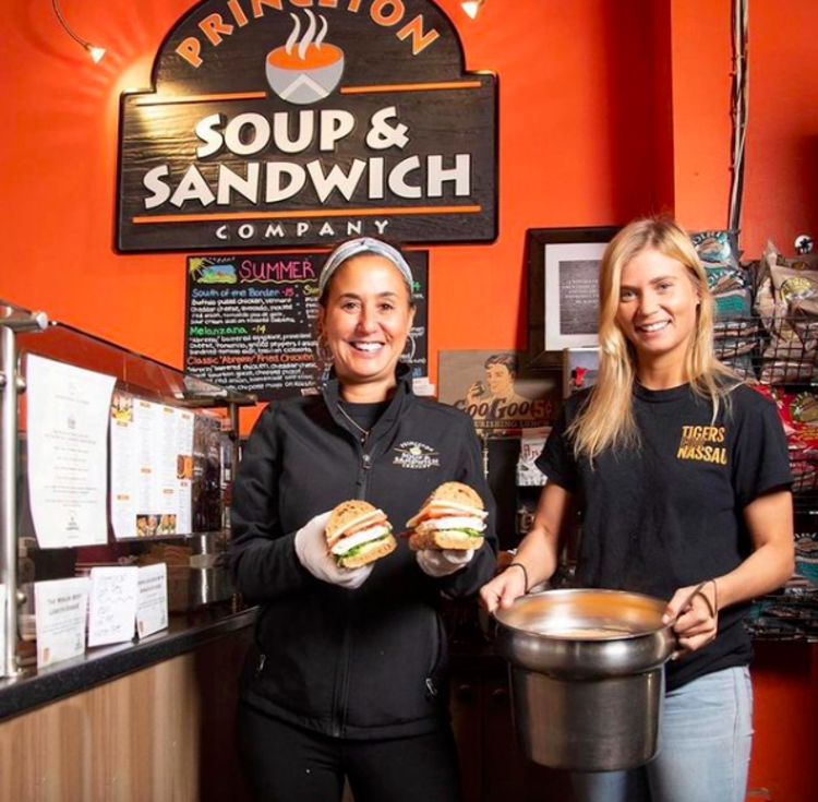 Smiling employees holding sandwiches in Princeton Soup and Sandwich