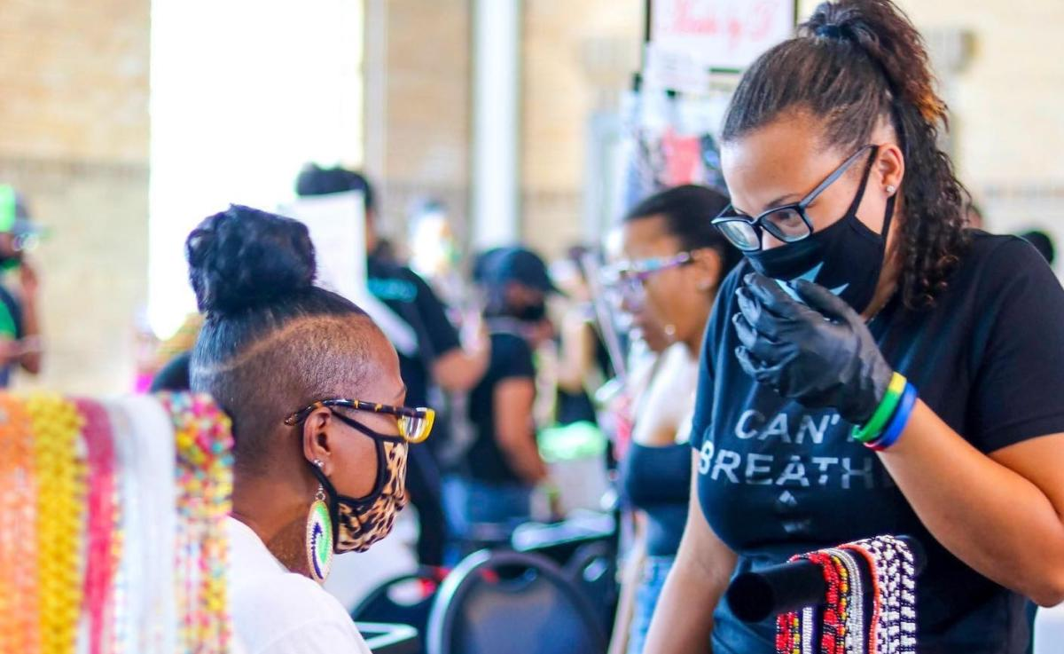 Two African-American women wearing face masks appear to be participating in a pop-up market.