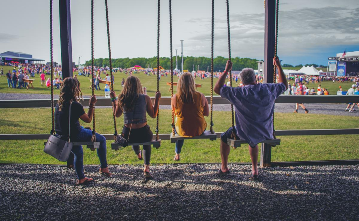 People sitting on wooden swings at Country Fest