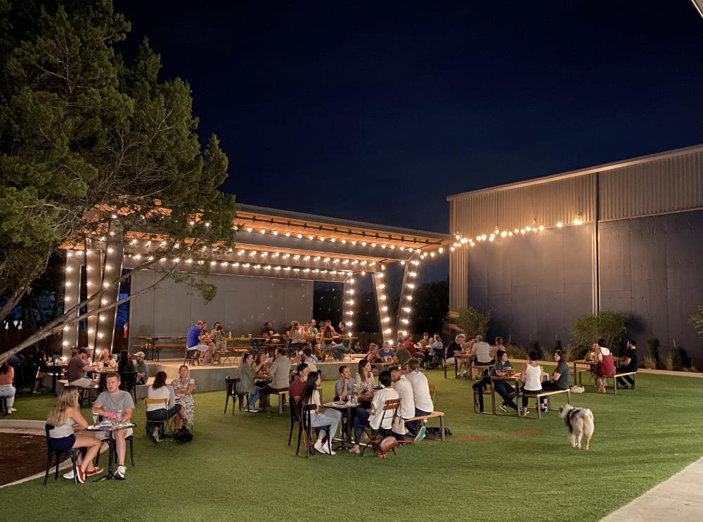 outdoor lawn at Meanwhile Brewing Co at night, with a stage and twinkle lights behind tables with people