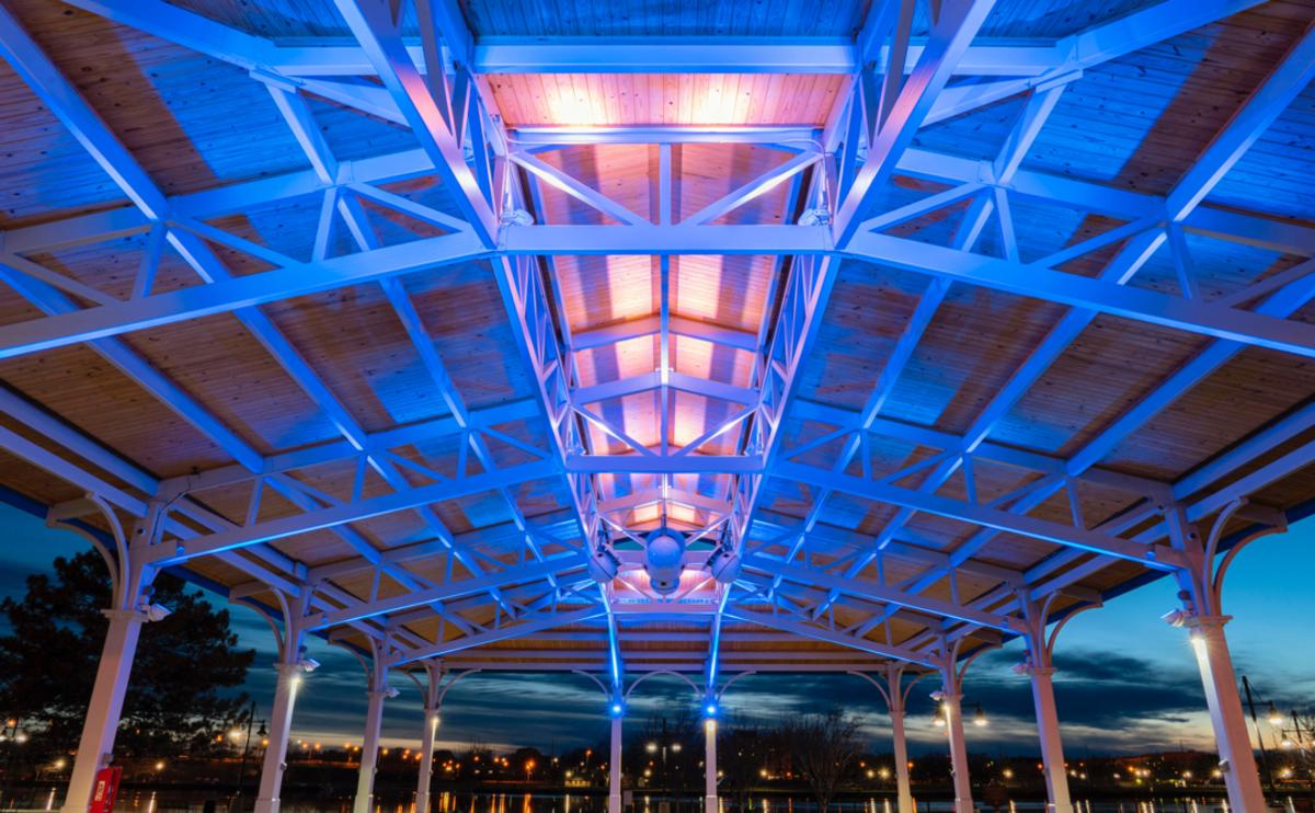 Views from beneath the colorfully lit Nickless Family Community Pavilion ice-skating rink in Bay City's Wenonah Park, with gorgeous views of the waterfront at dusk