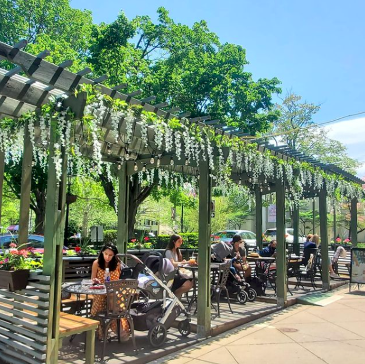 Outdoor tables with flowers draped over the roof